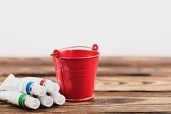 Högen av färgrika akrylmålarfärger i stängda behållare och röd tom metall ösregnar arkivbild