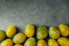 Högen av färgrika nytt valda körsbärsröda plommoner på svarta grå färger stenar bakgrund Begrepp för överflöd för höstnedgångskör royaltyfri fotografi