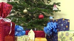 Högen av gåvor framlägger askar under dekorerat julgranträd arkivfilmer