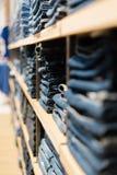 h?gen av jeans p? shoppar f?nstret i lagret arkivfoton