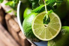 Högen av mogna organiska limefrukter klippte i halva i solljuset, lämnar nolla Arkivfoto