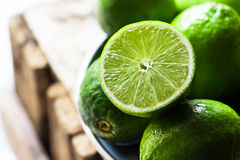 Högen av mogna organiska limefrukter klippte i halva i solljuset, på vintag Royaltyfria Foton