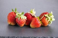 Högen av mogna röda jordgubbar kritiserar på svart tavla arkivbilder