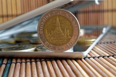 Högen av mynt med en främre myntvalör av baht 10 i spegel reflekterar plånboklögner på träbambutabellbakgrund Royaltyfri Fotografi