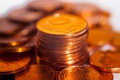 Högen av mynt mellan högen av att skina myntar pengarvärde Arkivbild