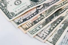 Högen av olika för dollarpengar för USA amerikanska räkningar fördelade som fansor Arkivbild