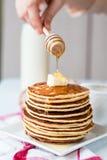 Högen av pannkakan med smör, honungsås tillfogar, händer Arkivbild