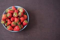 Högen av saftiga mogna organiska nya jordgubbar i en stor blått bowlar Stranda av hår vänder mot in Töm utrymme royaltyfria bilder