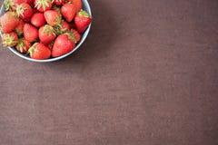 Högen av saftiga mogna organiska nya jordgubbar i en stor blått bowlar Stranda av hår vänder mot in Töm utrymme royaltyfria foton