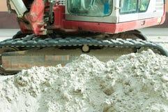 Högen av sand med grävskopan knäcker i bakgrunden på gatakonstruktionsplatsen Royaltyfria Bilder