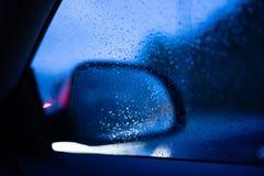 Höger bakre spegelsikt för bil från inre bilen med droppar på fönstret royaltyfria bilder