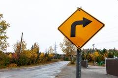 Höger gult vägmärke för vänd, som är vridet, bucklat, sprucket och rostigt - 1/2 fotografering för bildbyråer