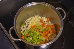 Högg av grönsaker i en soppakruka royaltyfria bilder