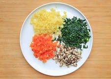 Högg av grönsaker på den vita plattan mot träbrädebakgrund royaltyfri foto