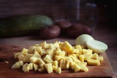 Högg av lökar och potatisar på en skärbräda royaltyfria bilder
