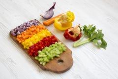 Högg av nya grönsaker som är ordnade på skärbräda på vit träyttersida, sidosikt arkivbilder