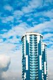 Höghus med en glass fasad mot en ljus blå himmel med figurerade moln Royaltyfria Foton