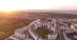 Höghus som omges av gröna fält och träd på solnedgången stock video