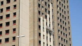 Höghusbyggmästare arbetar i en inställd vagga på en fasad av byggnad arkivfilmer