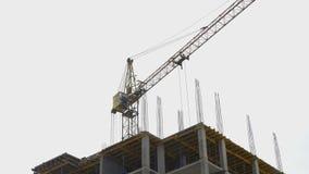 Höghuskran på konstruktionsplatsen av ett bostads- hus lager videofilmer