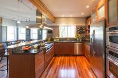 Högkvalitativt samtidahemkök med det wood kabinetter, ädelträgolvet, rostfritt stålanordningar, fönster och brytningbelysning royaltyfria bilder