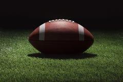 Högskolafotboll på gräsfält på natten med fläckbelysning Arkivfoto