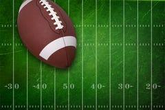 Högskolafotboll på texturerad fältbackgrou Arkivbild