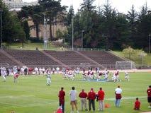 Högskolafotbollsspelare i handling som lagledareklockan Arkivfoto
