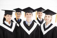 Högskolakandidat på avläggandet av examen med klasskompisar royaltyfria bilder