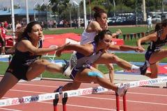 Högskolakvinnor som hoppar häckloppet royaltyfria foton