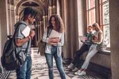 Högskolaliv Två lyckliga studenter som står och talar sig i ett universitet royaltyfria foton