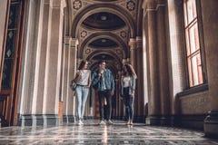 Högskolaliv Unga studenter som går i universitetet och att tala med de arkivfoton