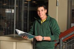 Högskolestudent Holding Textbook royaltyfri bild