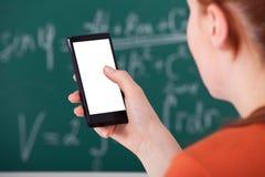 Högskolestudent som använder den smarta telefonen i klassrum Arkivbild