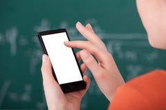 Högskolestudent som använder den smarta telefonen i klassrum Royaltyfri Bild