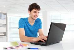 Högskolestudent som använder hans bärbar dator Royaltyfri Bild