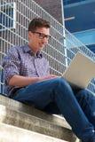 Högskolestudent som utomhus arbetar på bärbara datorn Arkivbilder