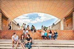 Högskolestudenter som har pratstunder på golvet bredvid byggnader royaltyfria foton