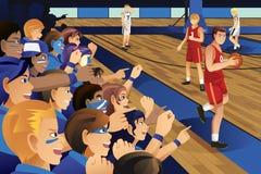 Högskolestudenter som hurrar för deras lag i en basketmatch Royaltyfri Foto