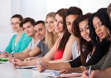 Högskolestudenter som i rad sitter på skrivbordet Arkivfoton