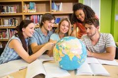 Högskolestudenter som pekar på jordklotet i arkiv arkivbild