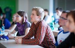 Högskolestudenter som sitter i ett klassrum under grupp Royaltyfria Foton