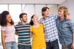 Högskolestudenter som står med armar omkring Arkivbilder