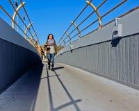 Högskolestudentkorsning bro royaltyfri foto