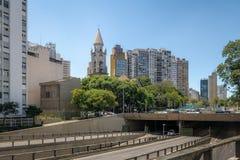 Högstämd huvudväg som är bekant som Minhocao Elevado Presidente Joao Goulart med den Nossa Senhora da Consolacao kyrkan - Sao Pau royaltyfri bild