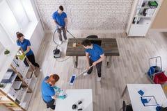 Högstämd sikt av dörrvakter som gör ren kontoret