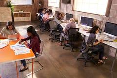 Högstämd sikt av folk som arbetar i kontor för modern design royaltyfria bilder