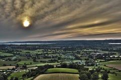 Högstämd solnedgångsikt över frodigt jordbruks- land Arkivbilder
