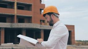 Högsta arkitekt på konstruktionsplatsen Högsta arkitekt i en hård hatt på konstruktionsplatsen som ser planet, ritning arkivfilmer