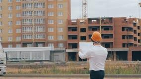 Högsta arkitekt på konstruktionsplatsen Högsta arkitekt i en hård hatt på konstruktionsplatsen som ser planet, ritning stock video